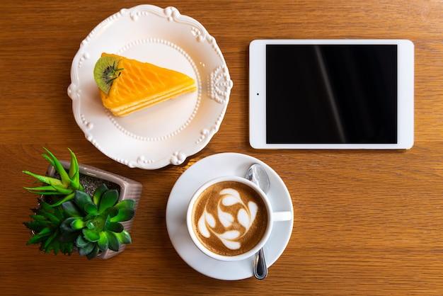 Lattekunstkaffee mit orange kuchen, tablette und blumentopf auf holztisch
