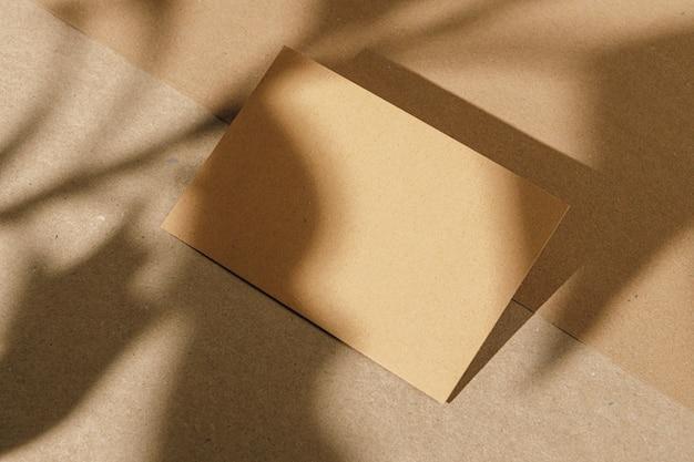 Laubschatten auf papierhintergrund mit visitenkarte