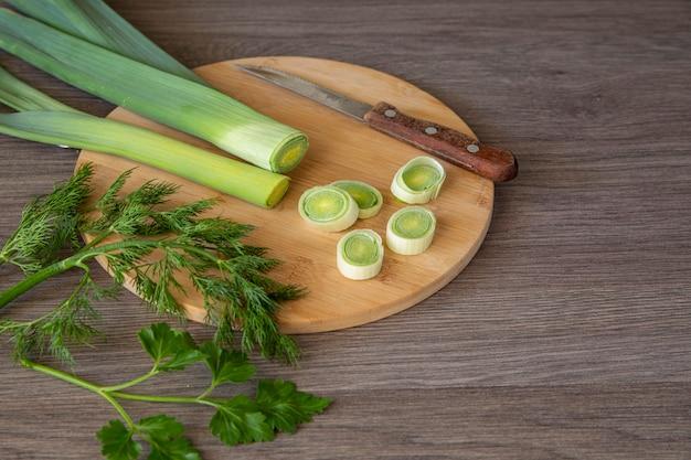 Lauch, dill und petersilie auf einem holzschneidebrett. vegetarisches essen. gesunder lebensstil