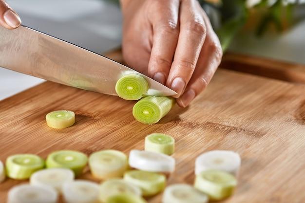 Lauchscheiben auf einem holzbrett auf dem küchentisch