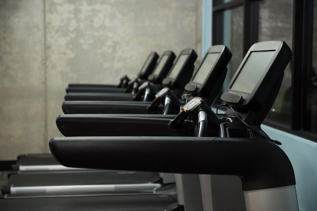 Laufbänder in reihe im leeren fitnessstudio
