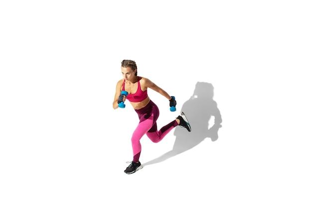 Laufen. schöne junge sportlerin, die auf weißer wand, porträt mit schatten übt. sportlich geschnittenes modell in bewegung und action. bodybuilding, gesunder lebensstil, stilkonzept.