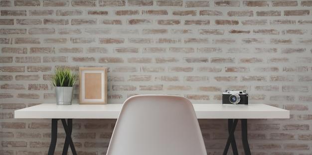 Laufen sie modernen arbeitsplatz mit weißem holztisch mit büroartikel und kopieren sie raum mit backsteinmauer