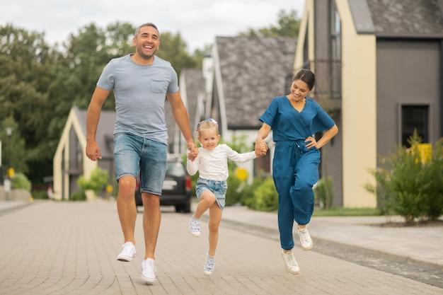 Laufen und spaß haben. tochter trägt jeansrock beim laufen, während sie spaß mit den eltern hat