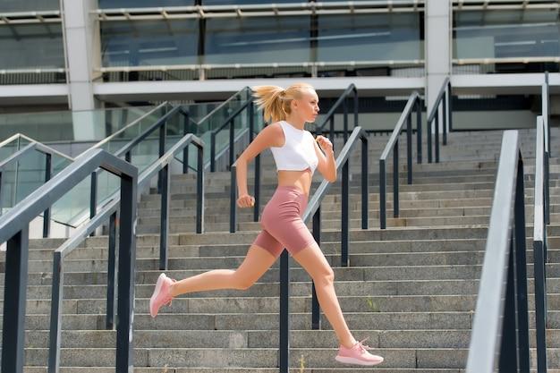 Laufen wie ein tier, sehen aus wie eine schönheit. energiegeladene frau läuft im stadion. schneller lauf. fit athlet in sexy sportkleidung. sportliche läuferin. training und training. fitness- und sportmotivation. lauf noch etwas.