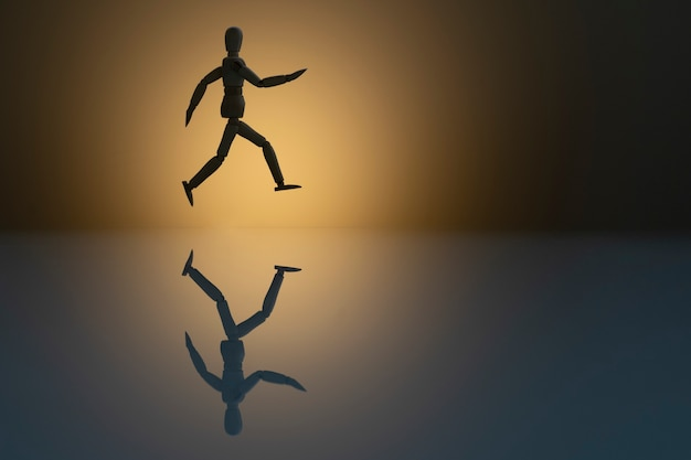 Laufende hölzerne dummy-silhouette mit reflexion im glas. rennen zum erfolgskonzept. olympia