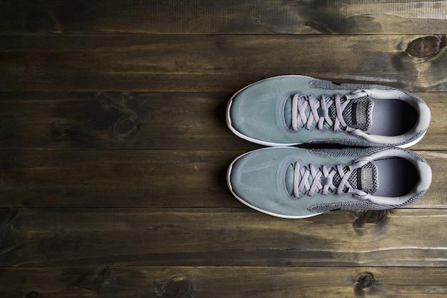 Laufende sportschuhe auf hölzerner hintergrund draufsicht mit kopienraum.