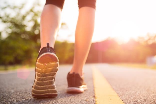 Laufende und gehende frauenbeine beim trainieren während des sonnenuntergangs.