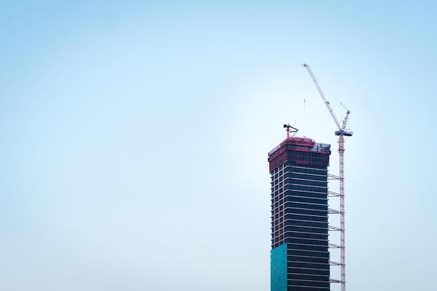 Laufender bau des wolkenkratzers in der modernen stadt mit hohen roten kränen, stahlrahmenstruktur und glaswand des außengebäudes mit klarem blauem himmel im hintergrund.