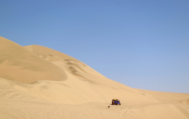 Laufender dünenbuggy, der durch einen frechen hund auf den sanddünen von huacachina-wüste, ica-region, peru jagt