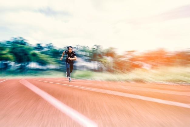 Laufender mann, der auf der bahn mit radialunschärfe, sport und tätigkeitskonzept läuft