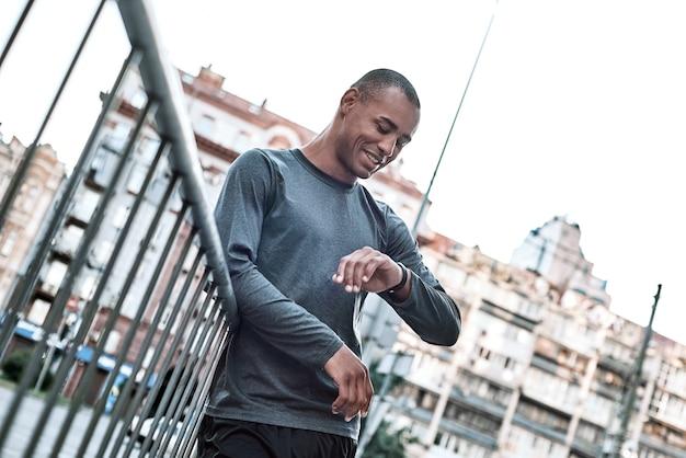 Laufender mann, der auf herzfrequenzmesser-gps-smartwatch-läufer auf stadtprogrammierungs-smartwatch schaut