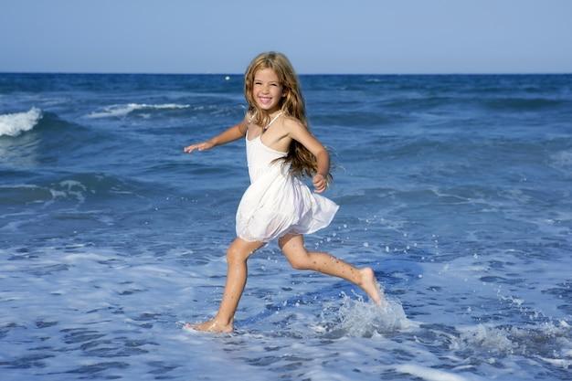 Laufender strand des kleinen mädchens im blauen meer
