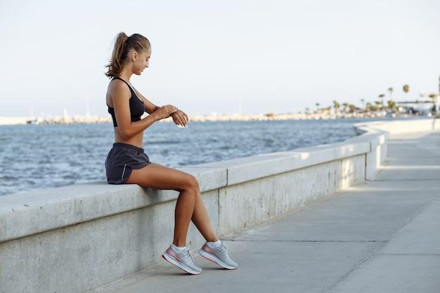 Laufendes mädchen mit smartwatch, das sich nach dem joggen ausruht