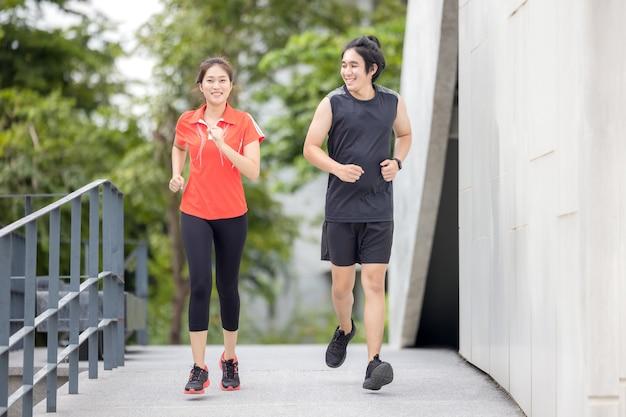 Laufendes paar, das draußen in der stadt in einem aktiven sportfoto des städtischen lebens trainiert, mit gebäuden im hintergrund