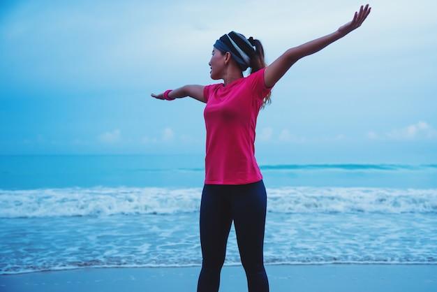 Laufendes training der asiatinnen, das morgens auf dem strand rüttelt
