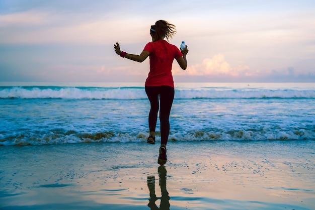 Laufendes training des mädchens, das morgens auf dem strand rüttelt.