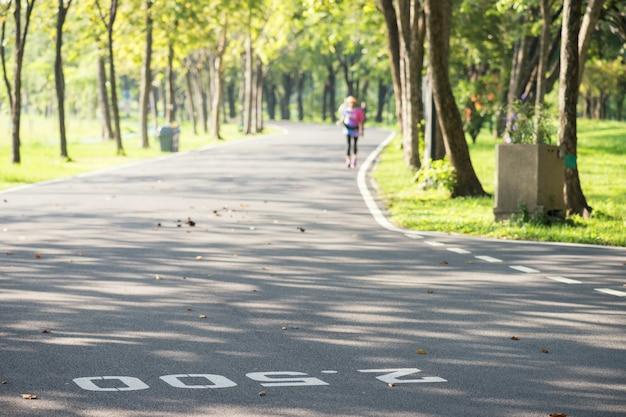 Laufpfad des sommerparks mit meilenstein gemalt auf straße mit unscharfem laufendem athleten am morgen. sport und gesunder lebensstil.