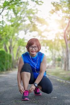 Laufschuhe - ältere asiatische frau, die durch den park rüttelt, der schnürsenkel bindet