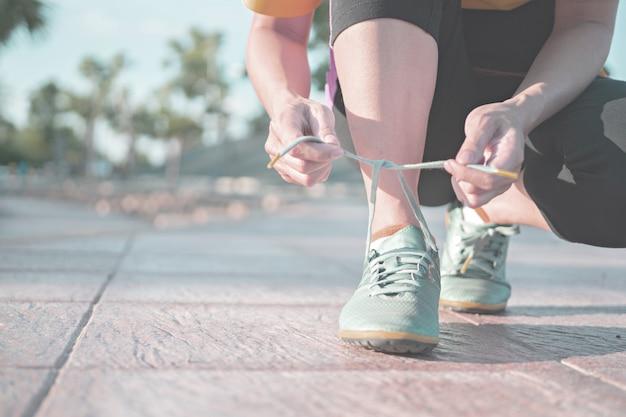 Laufschuhe - frau, die schnürsenkel bindet. nahaufnahme des weiblichen sporteignungsläufers, der zum draußen rütteln fertig wird.
