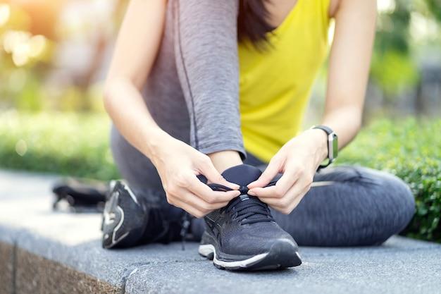 Laufschuhe - frau, die schnürsenkel bindet, sportlicher eignungsläufer, der zum rütteln am garten fertig wird.