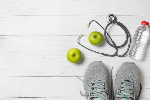 Laufschuhe mit grünen äpfeln und stethoskop nahe süßwasserflasche, übung und diätkonzept