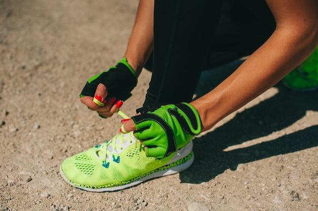 Laufschuhe - nahaufnahme der frau, die schnürsenkel bindet. weiblicher sporteignungsläufer, der zu draußen auf waldweg im frühjahr oder sommer draußen rütteln fertig wird.
