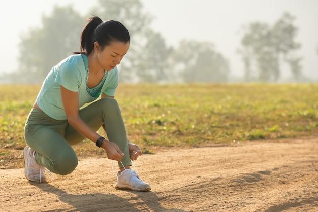 Laufschuhläuferfrau, die schnürsenkel für den herbstlauf im waldpark bindet. läufer, die laufschuhe ausprobieren, bereiten sich auf den lauf vor. joggen mädchen übung motivation gesundheit und fitness.