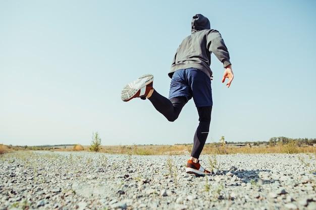 Laufsport. mannläufer, der im freien in der landschaftlich reizvollen natur sprintet. fit muskulöses männliches athleten-trainings-trailrunning für den marathonlauf. sportlich fit sportlicher mann, der im sprint in kompressionskleidung trainiert