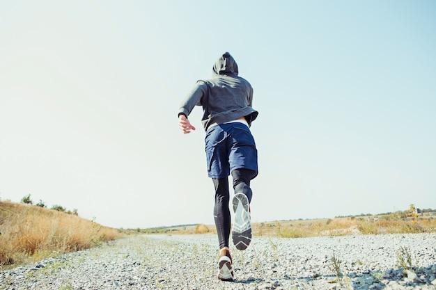 Laufsport. mannläufer, der im freien in der landschaftlich reizvollen natur sprintet.