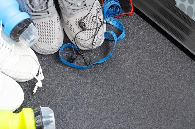 Laufstrecke mit turnschuhen und einer flasche wasser auf schwarzem hintergrund. übungsgeräte für die gesundheit. studiofoto.