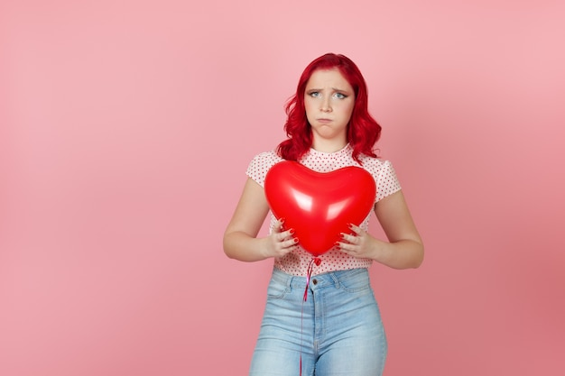 Launische frau mit roten haaren und jeans hält einen fliegenden roten ballon in den händen und bläst ihre wangen auf