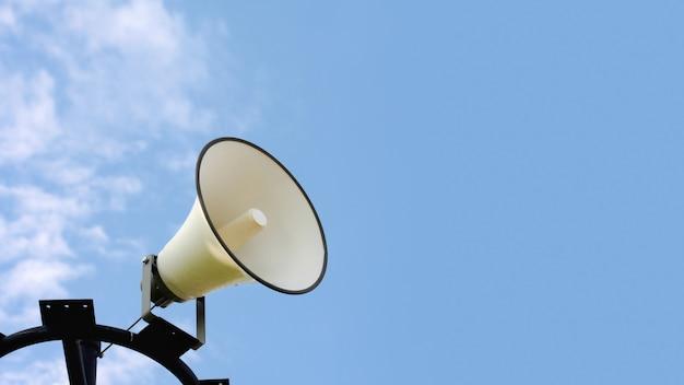 Lautsprecher auf einer stange im blauen himmel