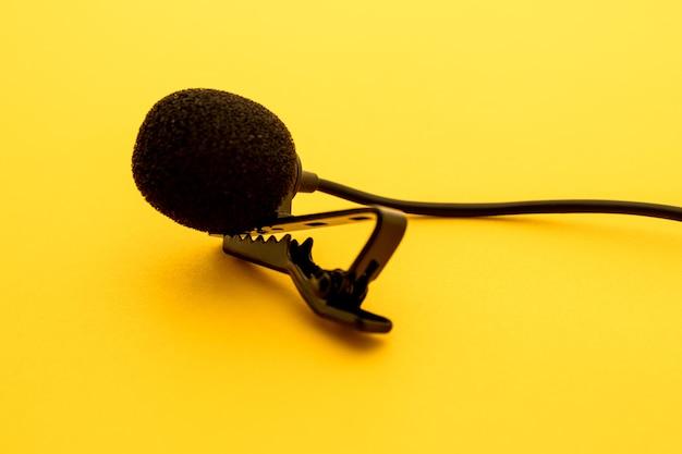 Lavalier- oder ansteckmikrofon auf gelber oberfläche, sehr nah. die details des griffclips oder bhs und des schwamms gegen den wind sind sichtbar.