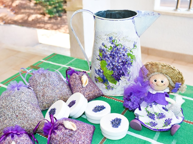 Lavanda-souvenirs von der insel hvar, kroatien. lavander festival. getrocknete lavanda in der tasche, lustige puppe, karaffe, kosmetikgläser auf dem tisch