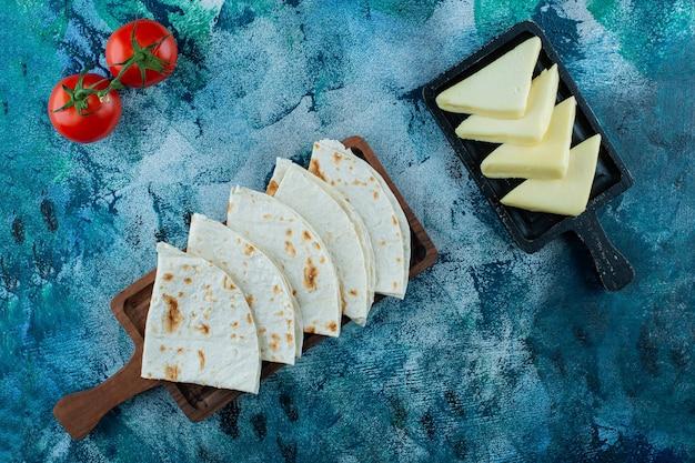 Lavash auf einem brett und köstlicher käse auf einem brett neben tomaten, auf dem blauen hintergrund.