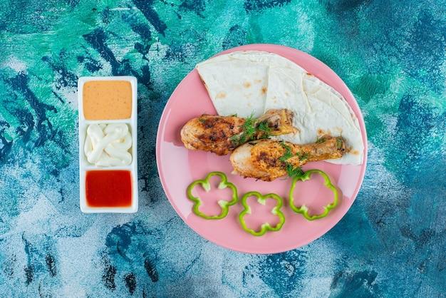 Lavash, gebackene drumsticks und pfeffer auf einem teller neben saucenschalen auf der blauen oberfläche