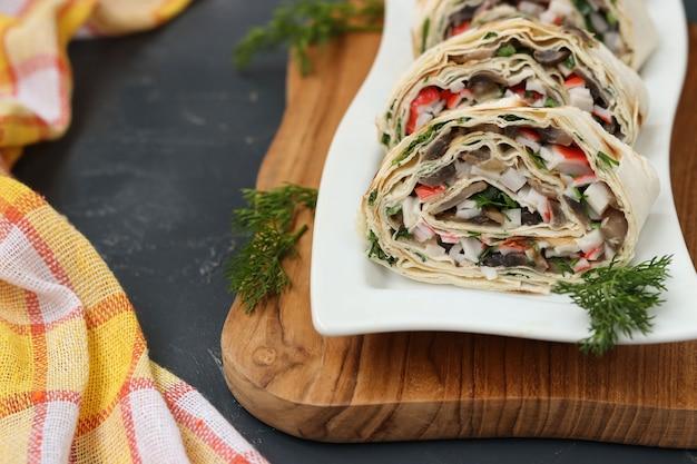 Lavash roll mit champignons, krabbenstangen und käse, festliche vorspeise, nahaufnahme