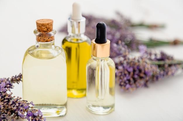 Lavendel ätherisches öl flaschen, serum, tropfer auf weißen rustikalen holztisch frische lavendelblüten. aromatherapie-behandlung, natürliche spa-kosmetik, apotheker-lavendelkraut. hautpflege haarkosmetik.