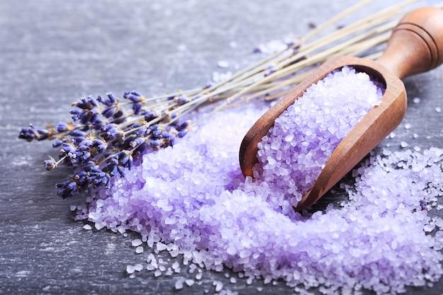 Lavendel badesalz und getrocknete lavendelblüten im dunkeln