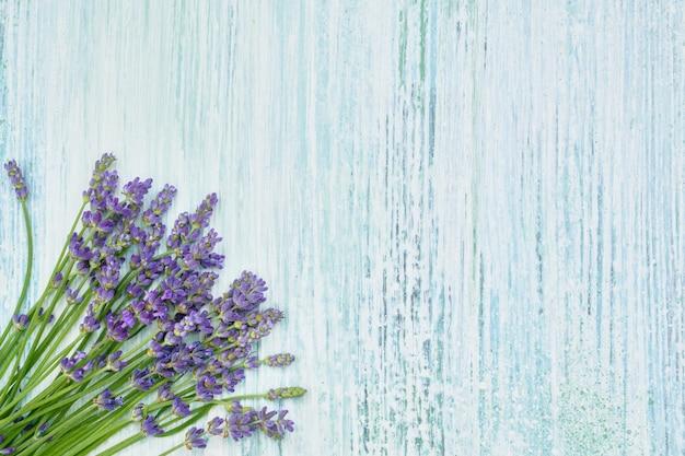 Lavendel blüht blumenstrauß auf blauem hölzernem hintergrund. exemplar, ansicht von oben.