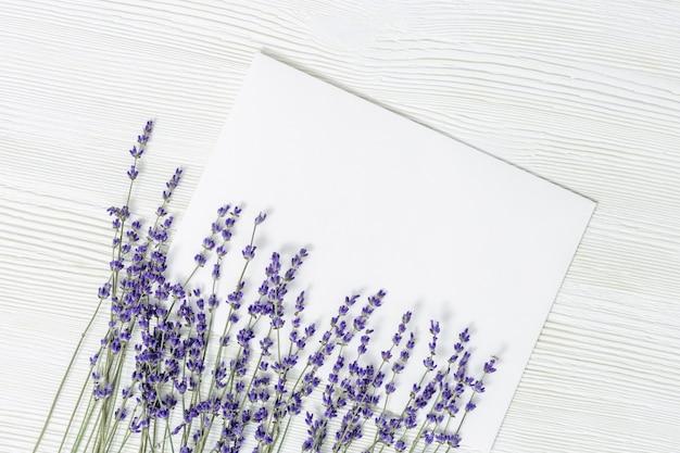Lavendel blüht mit blatt des leeren papiers auf weißem holztisch mit kopienraum.