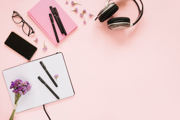 Lavendel blumenstrauss; handy; kopfhörer und schreibwaren auf rosa hintergrund