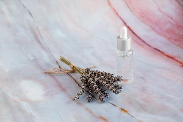 Lavendel entspannende heilmittel. aromawasser und -öl in den flaschen mit den lavendelzweigen flaschen über marmorhintergrund. lavendelöl. feuchtigkeitscreme mit vitaminen und kräuteressenz. ätherisches öl. vitamin c. beauty