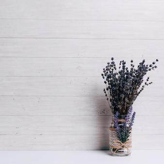 Lavendel im glas auf schreibtisch gegen hölzernen hintergrund