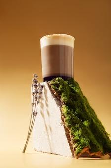 Lavendel-latte-getränk mit sirup auf beigem stein mit holzrindenmoos und lavendelblüten. konzept von natürlichkeit und modernität