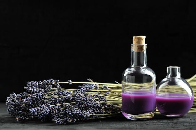 Lavendel, lavendelöl auf dunklem hölzernem hintergrund mit raum für text