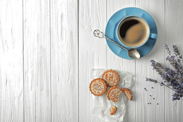 Lavendel mit kaffee und keksen auf hölzernem hintergrund