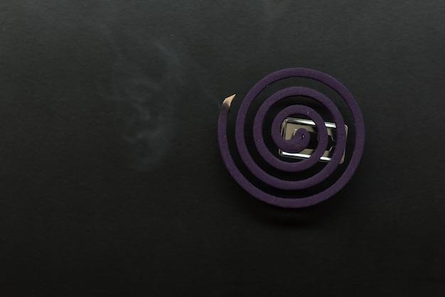 Lavendel mückenschutz mit rauch auf dunklem hintergrund