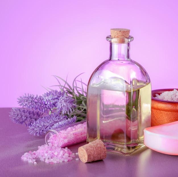 Lavendel-spa-produkte mit natürlichem öl, seife, meersalz und lavendelblüten auf dem tisch.